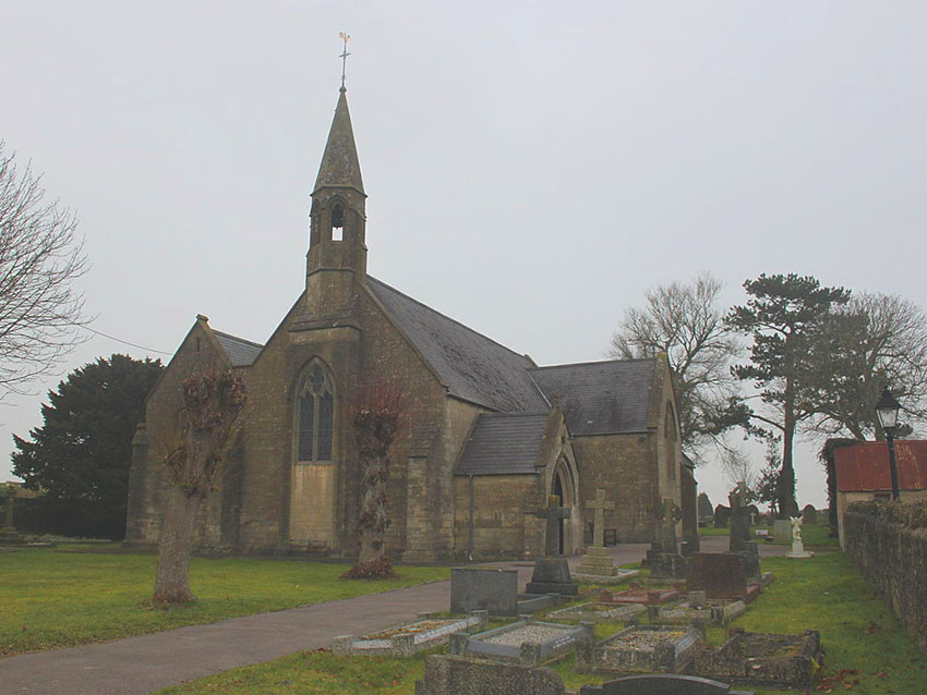 a traditional church building on a cludy day surrounded by a cemetery
